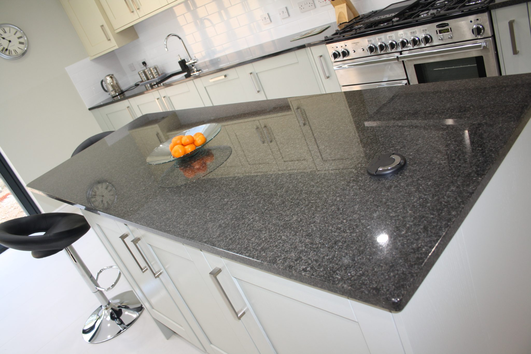 image of black granite worktops with stark white floor and pale grey units