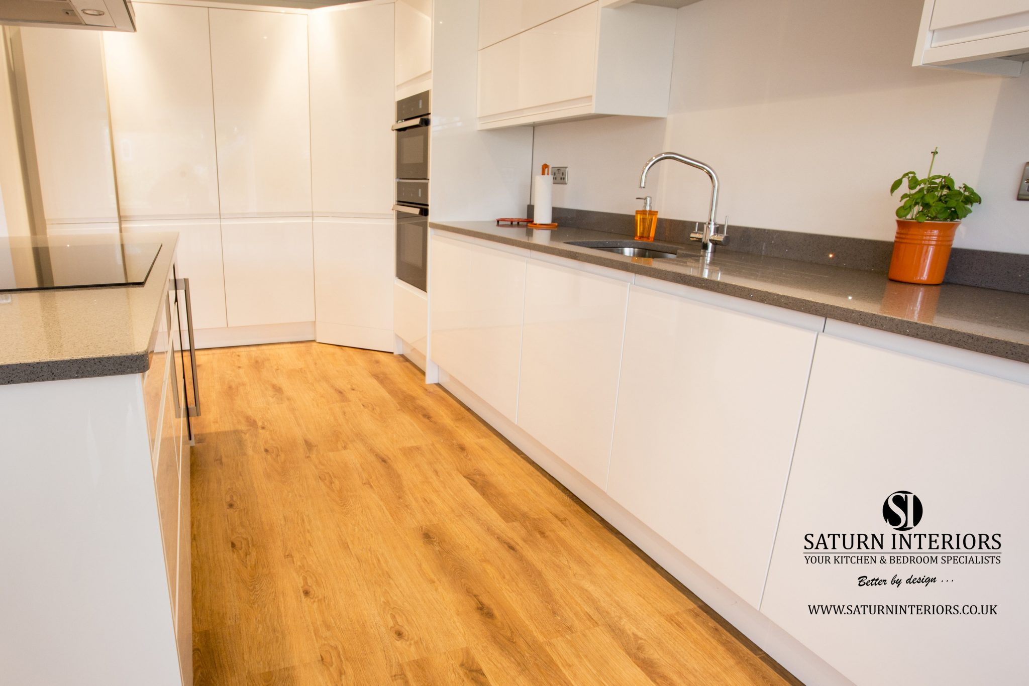 image of white kitchen units with quartz worktop and wood floor