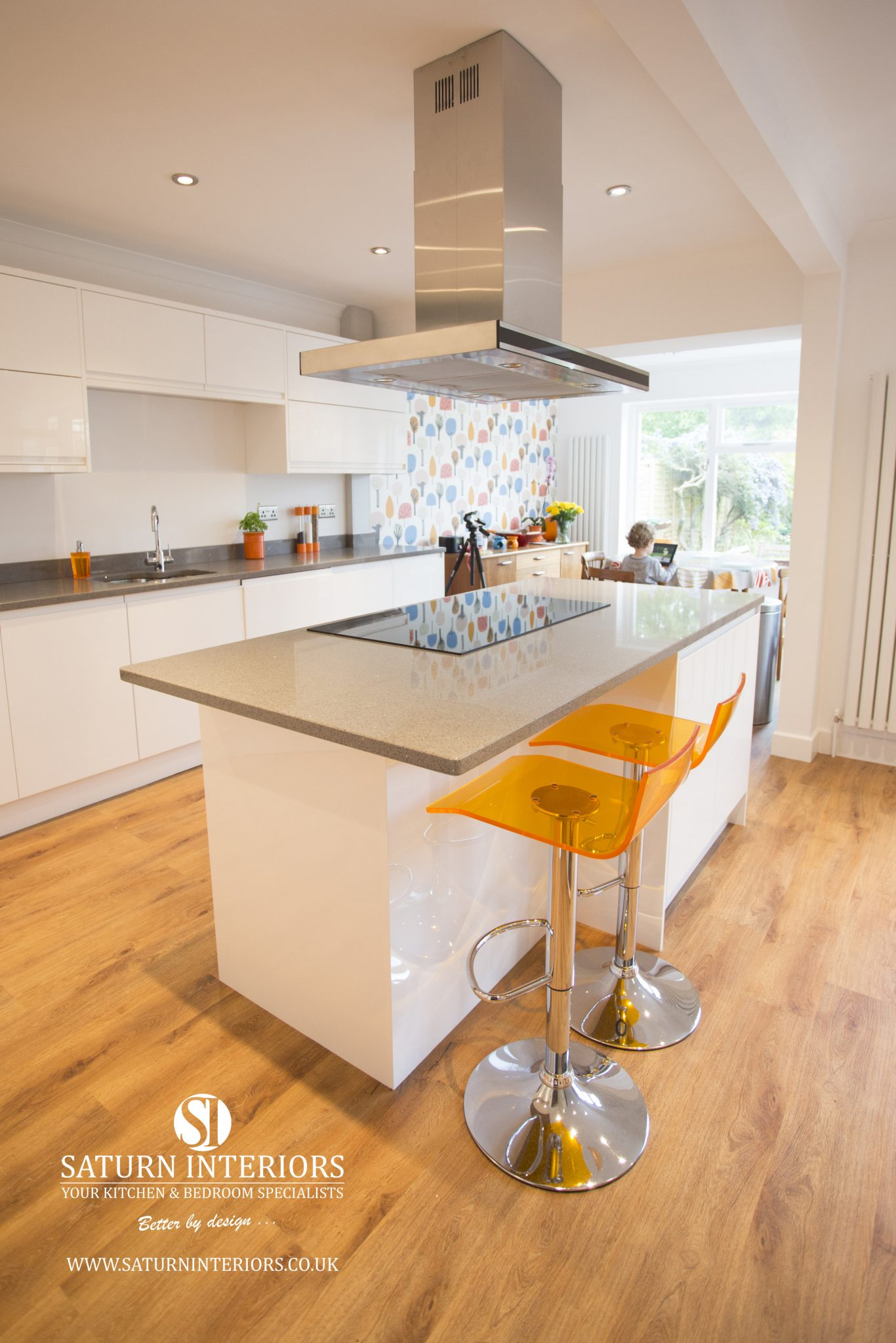 image of white kitchen units with grey worktop and wooden flooring
