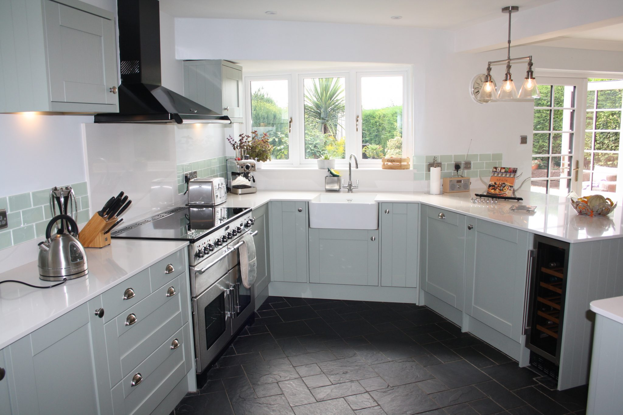 image of duck egg blue kitchen units with white work top, butler sink and dark stone tile floor