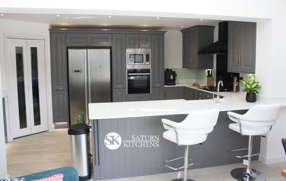 image of modern kitchen with grey units, white worktops, light wood floor and breakfast bar