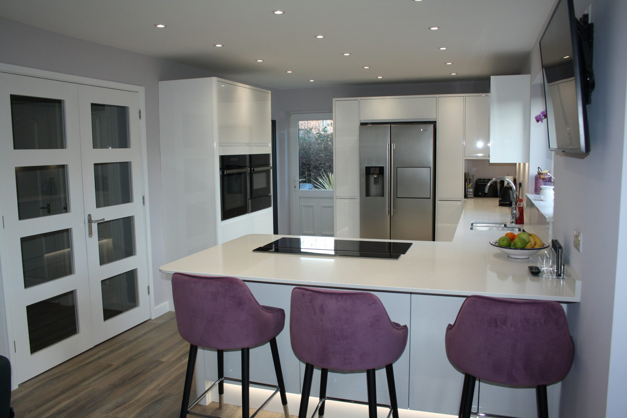 image of modern kitchen with white units, white worktops, wood floor, under unit lighting and breakfast bar