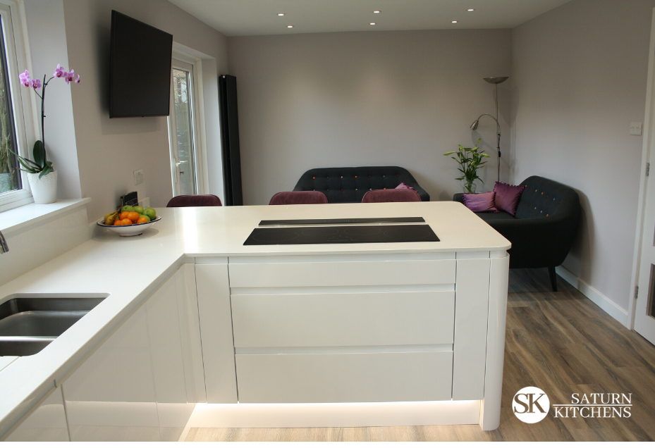 image of modern kitchen with white units, white worktops, wood floor and under unit lighting