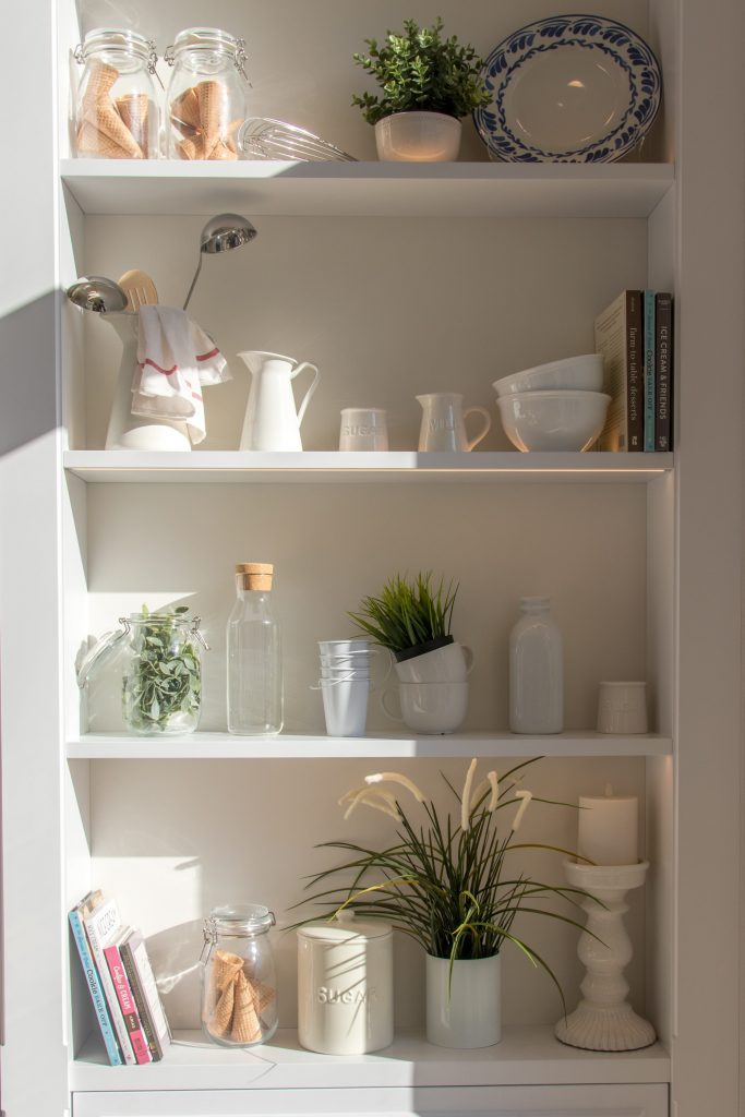 White ceramic bowls and bottles along with other glassware perfectly arranged on the pantry.