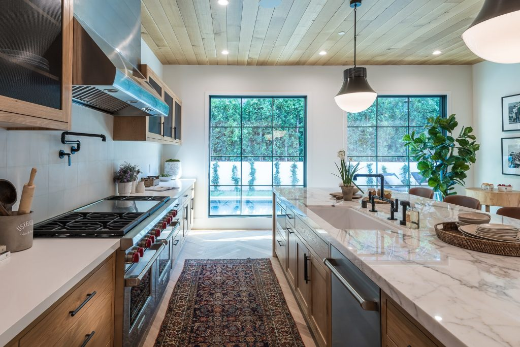 kitchen with floor to ceiling glass windows, a huge granite worktop with plants placed around the space