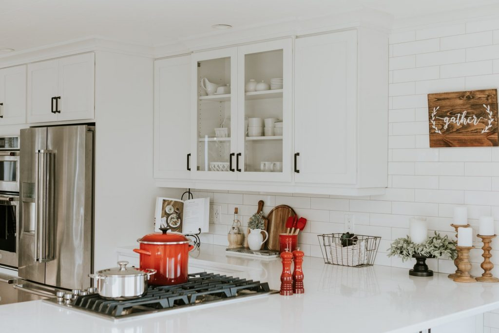 white kitchen cabinets done in a minimalist manner, red crockery for the perfect transitional kitchen
