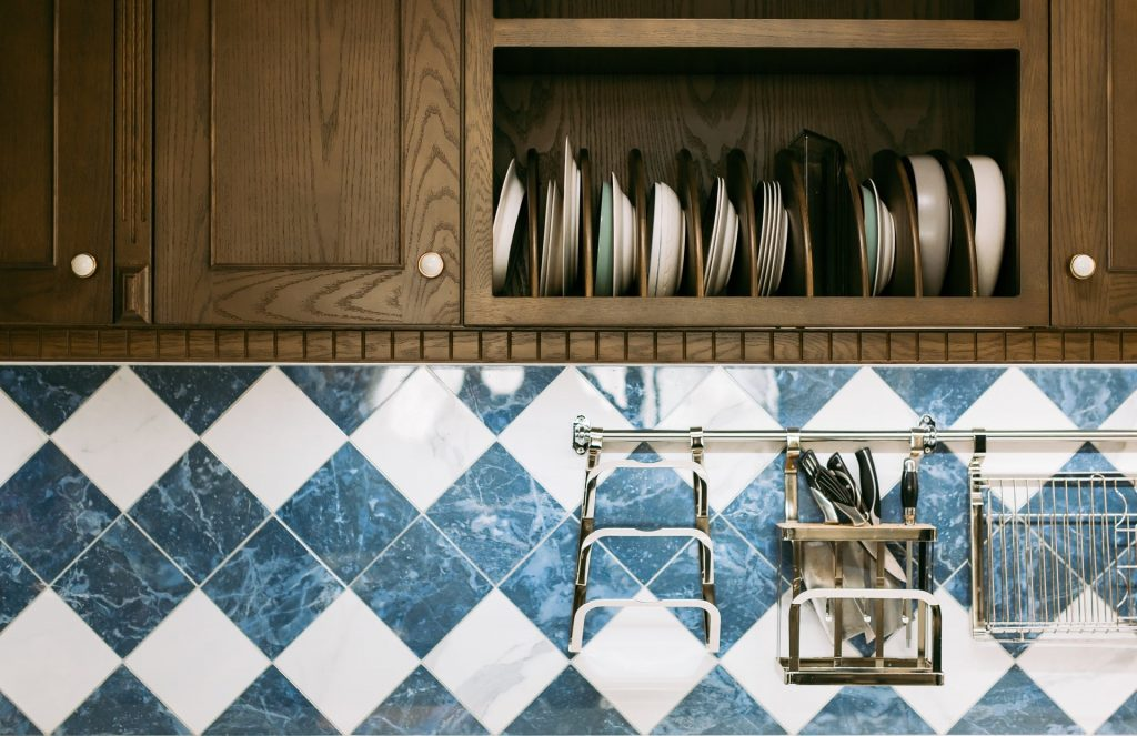 combination of blue and white tiles creating and attractive texture in the kitchen space, wooden cabinets with dishes on display