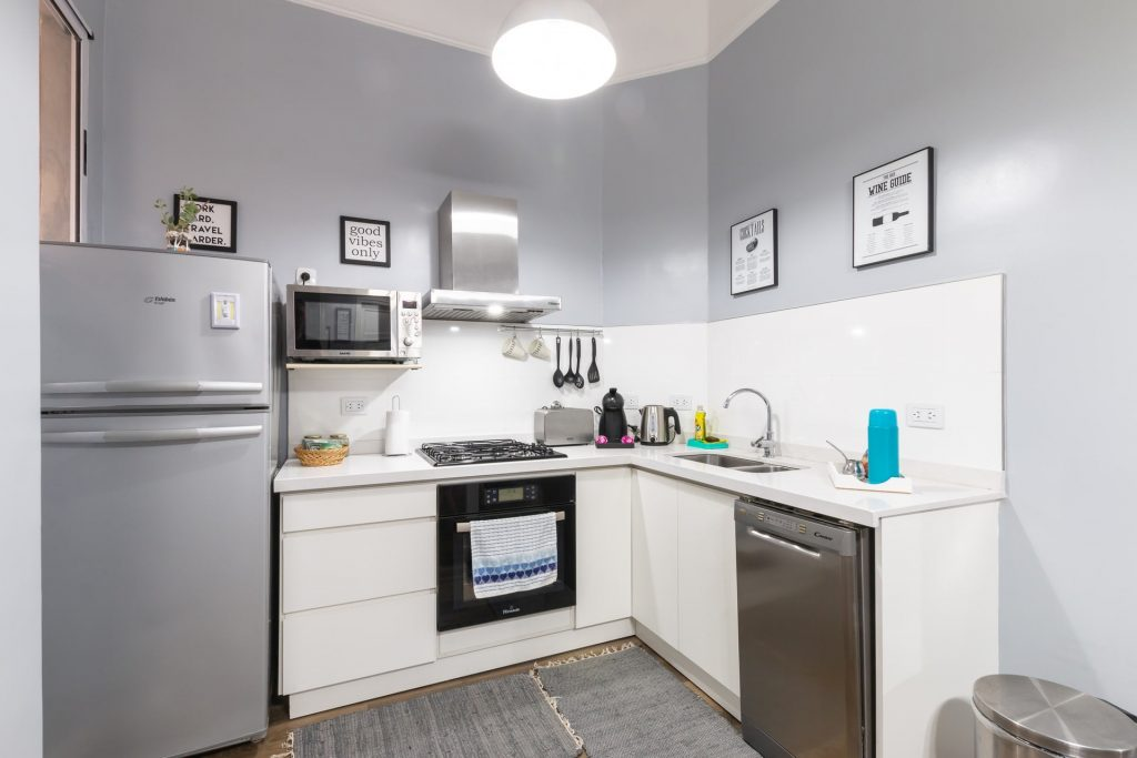 small kitchen space with stainless steel oven, toaster and fridge