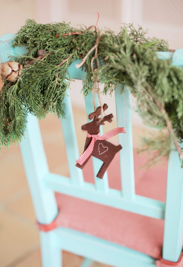 Kitchen chair decorated using wooden reindeer and holly
