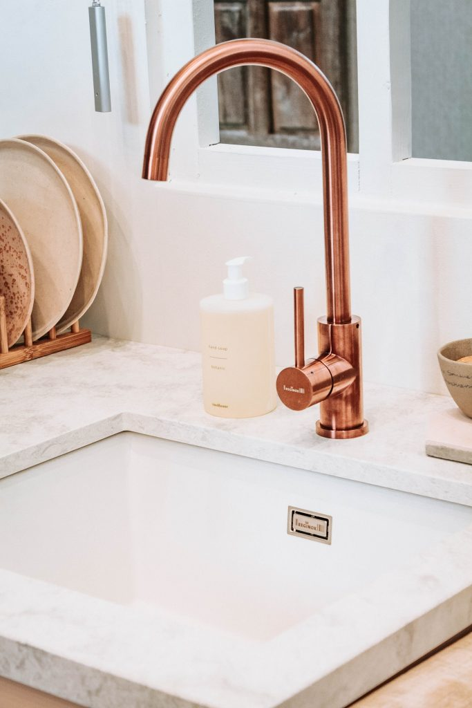 A brass faucet is an example of how kitchens can make use of durable materials to last longer.
