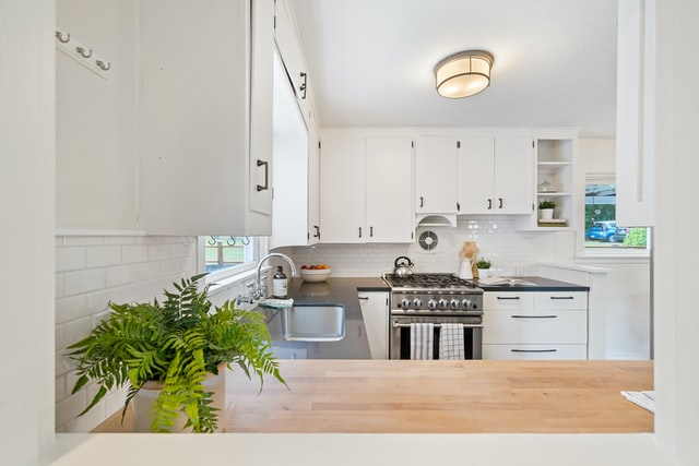 all-white kitchen featuring reclaimed contuertop and white cabinets