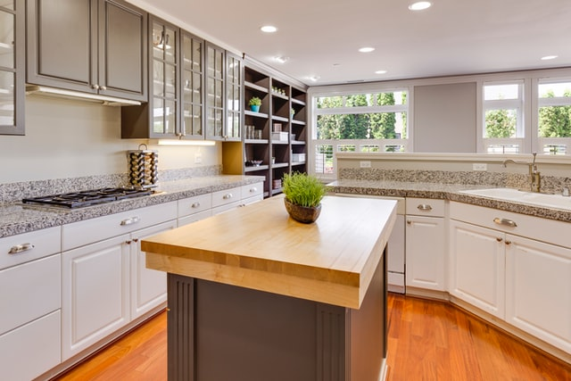 kitchens and pets, brown countertop placed in the centre of an all-white kitchen