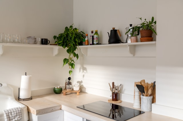 an all white kitchen featuring open shelves