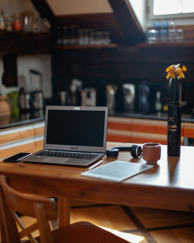 modern kitchen designs, laptop and headphones placed on a brown kitchen table